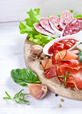 Sliced prosciutto in white wooden background Royalty Free Stock Images