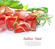 Sliced prosciutto in white wooden background Royalty Free Stock Photos