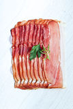 Sliced prosciutto in white wooden background Stock Photography