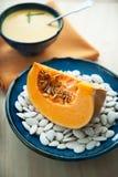 Sliced pumpkin. A piece of pumpkin on a plate with pumpkin seeds Royalty Free Stock Photography