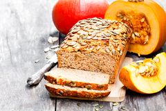 Sliced  pumpkin  bread loaf on wooden cutting board with seeds Royalty Free Stock Images