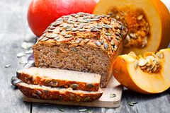 Sliced  pumpkin bread loaf on wooden cutting board with seeds Royalty Free Stock Photos