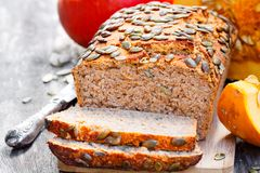 Sliced  pumpkin  bread loaf on wooden cutting board with seeds Royalty Free Stock Image