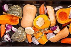 Sliced Pumpkin, carrot, onion, garlic and rosemary on black tray Stock Photography