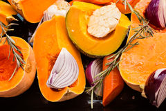 Sliced Pumpkin, carrot, onion, garlic and rosemary on black tray Stock Photo