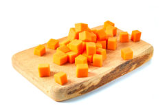 Sliced pumpkin cubes on wooden board ower white background. Sliced pumpkin cubes on wooden board. Isolated on white background stock photos