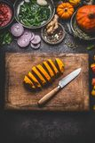 Sliced pumpkin on cutting board with knife and various vegetables and seasoning ingredients for tasty seasonal dish cooking, rusti Stock Photography