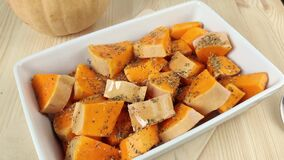 Sliced pumpkin with dried spices is watered with oil. Cooking orange baked pumpkin in white rectangular dish. Healthy vegetable,