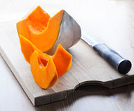 Sliced Pumpkin and knife on a wooden board.  Stock Photos