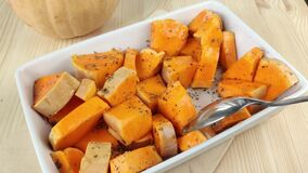 Sliced pumpkin with oil and dried spices is stirred with spoon. Cooking orange baked pumpkin in white rectangular dish. Healthy