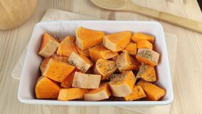 Sliced pumpkin with oil and salt sprinkled with dried herbs and spices. Cooking orange baked pumpkin in white rectangular dish.
