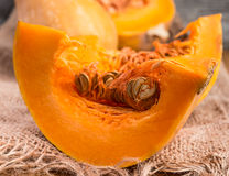 Sliced pumpkin on rustic table and burlap Royalty Free Stock Images