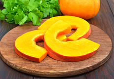 Sliced pumpkin on wooden cutting board Royalty Free Stock Images