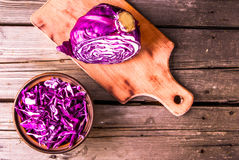 Sliced purple cabbage in a bowl, and the residue of it on a cutting board. Vitamin autumn meal. Copy space, top view, on wooden table Royalty Free Stock Photos