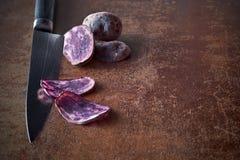 Sliced purple potatos, two slices on knife and two whole potatos. Sliced negresse or vitelotte potatos, that have purple flesh. Two slices on knife, potatos on Royalty Free Stock Photos