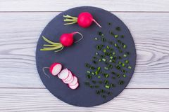 Sliced radish and green onion, top view. Spring onion and radish on black slate board. Cooking vitamin salad Royalty Free Stock Photo