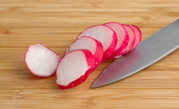 Sliced radish on a wood cutting board Royalty Free Stock Photo
