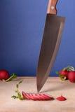 Sliced radishes on cutting board, kitchen knife. Close up, blue background. Sliced garden radishes on cutting board, kitchen knife. Close up, blue background Stock Image
