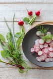 Sliced radishes on a dark plate on a white wooden table stock photography