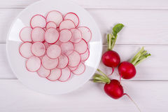 Sliced Radishes on white plate  ready for salad. Top view Stock Images