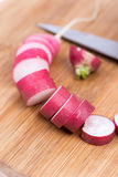 Sliced radishes on the wooden board.  Stock Photos