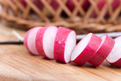 Sliced radishes on the wooden board.  Royalty Free Stock Photo