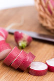 Sliced radishes on the wooden board.  Royalty Free Stock Photos