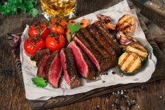 Sliced rare grilled steak with grilled vegetables and whiskey Stock Photo