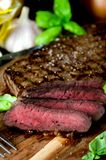 Sliced rare steak pepper salt garlic basil. On a dark background Royalty Free Stock Photography