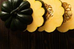 Sliced raw acorn squash on dark background Royalty Free Stock Photo