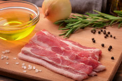 Sliced raw bacon, olive oil, spices and herbs. Still life with sliced raw bacon, olive oil, spices and herbs Stock Image
