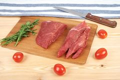 Sliced raw beef on cutting board and vegetables.  Royalty Free Stock Photos