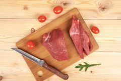 Sliced raw beef on cutting board and vegetables.  Stock Photos