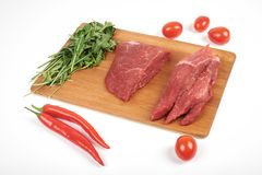 Sliced raw beef on cutting board and vegetables isolated on white background.  Stock Photography