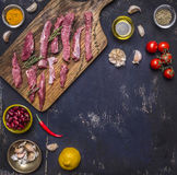 Sliced raw beef with lemon, tomatoes and spices frame, border, place for text on wooden rustic background top view Royalty Free Stock Photography