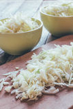 Sliced raw cabbage on the old cutting Board and ceramic bowls close up Royalty Free Stock Photography