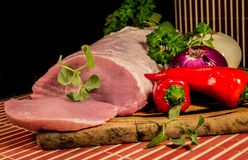 Sliced raw meat on wooden board. Peppers,Onion and herbs Stock Image