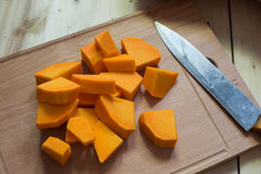 Sliced raw orange pumpkin on cutting board Stock Images
