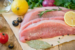 Sliced raw pork with spices on a rustic table. Stock Photos