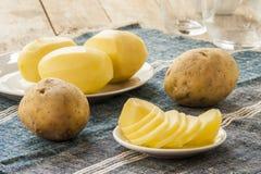Sliced raw potato on kitchen table Royalty Free Stock Photo