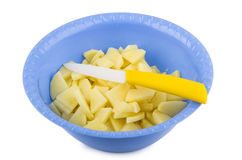 Sliced raw potatoes and knife in plastic bowl Stock Image