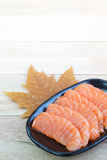 Sliced raw salmon on black plate with wood background Royalty Free Stock Photo
