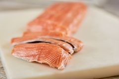 Sliced raw salmon on cutting board. Fresh salmon fillet on cutting board. Restaurant of seafood Royalty Free Stock Images