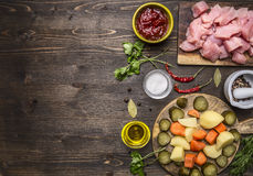 Sliced raw turkey with potatoes, carrots and pickles, ingredients for stew border ,place text on wooden rustic background top. Sliced raw turkey with potatoes royalty free stock photography