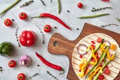 Sliced raw vegetables on a tortilla on a wooden board. Royalty Free Stock Image