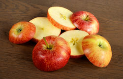 Sliced red apples. Red apples cut into slices on a wooden substrate Royalty Free Stock Images