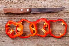 Sliced red bell peppers and old knife Royalty Free Stock Photography