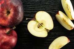Fresh raw red delicious apple on black wood. Sliced red delicious apples flatlay on black wood background two whole one half and three slices Royalty Free Stock Photos