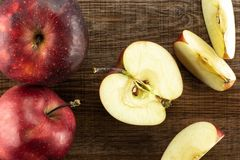 Fresh raw red delicious apple on brown wood. Sliced red delicious apples flatlay on brown wood background two whole one half and three slices Stock Image