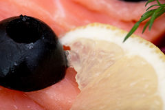 The sliced red fish salmon greens lemon black olives close-up, macro Stock Image